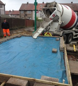 Pouring cement on brick garage foundations